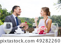 man giving woman engagement ring at restaurant 49282260