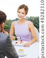 woman looking at man and eating cake at restaurant 49282310