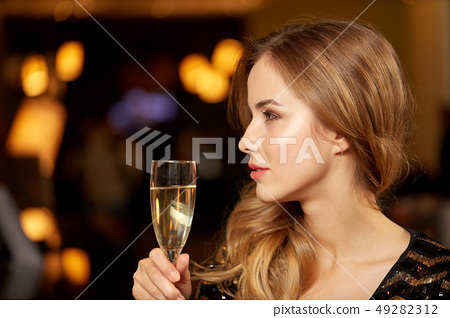 woman with glass of champagne at night club 49282312