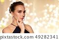 beautiful woman in black wearing diamond jewelry 49282341