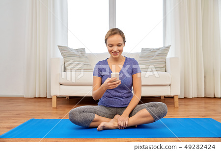 woman with smartphone doing yoga at home 49282424