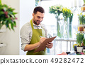 florist man with clipboard at flower shop counter 49282472