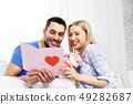 happy couple with greeting card and flowers 49282687