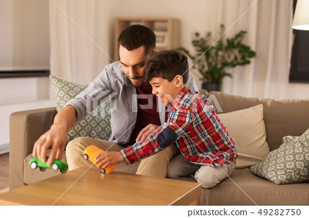father and son playing with toy cars at home 49282750
