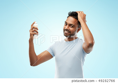 smiling indian man applying hair spray over blue 49282766