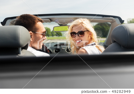 happy man and woman driving in cabriolet car 49282949