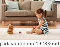 little girl playing with toy tea set at home 49283660