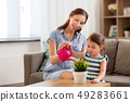 pregnant mother and daughter watering home plant 49283661