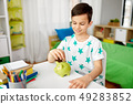 little boy putting coin into piggy bank at home 49283852