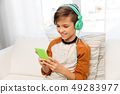 happy boy with smartphone and headphones at home 49283977