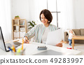 mother working with papers and baby boy at home 49283997