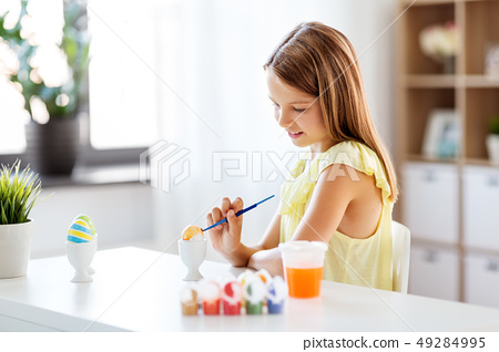 happy girl coloring easter eggs at home 49284995