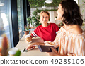female friends paying by credit card at cafe 49285106