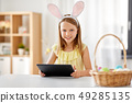happy girl with tablet pc and easter eggs at home 49285135