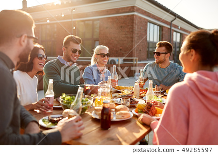 happy friends with drinks or bbq party on rooftop 49285597