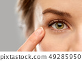 close up of woman pointin finger to eye 49285950