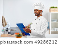 indian chef reading menu on clipboard at kitchen 49286212