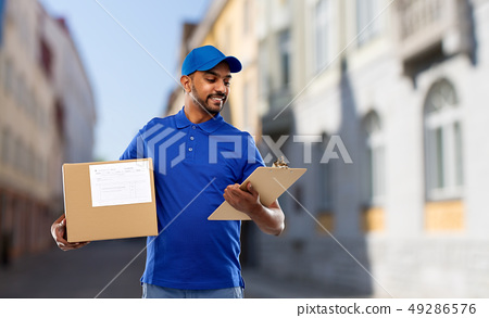 delivery man with parcel and clipboard in city 49286576