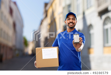 delivery man with smartphone and parcel in city 49286579