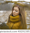Pretty woman in a yellow knit scarf.  49291395