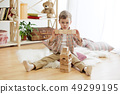 Little child sitting on the floor. Pretty boy palying with wooden cubes at home 49299195