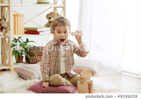 Little child sitting on the floor. Pretty boy palying with wooden cubes at home 49299209
