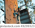 Active young woman on rock wall in sport center 49299323