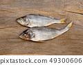 Two dried fishes on a wooden table. 49300606