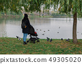 A woman walks in the park with a stroller and a 49305020