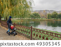 A woman walks in the park with a stroller and a 49305345