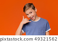 Flirty boy making call me gesture, orange background 49321562
