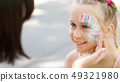 Cute little girl getting her face painted in park 49321980