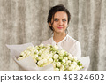 beautiful brunette woman with a bouquet of tulips flowers 49324602