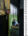 Young male prisoner sitting alone in an obsolete prison cell 49339400