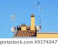 Satellite antenna and old roof antenna on a red roof 49374047