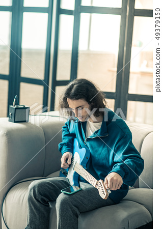 Dark-haired handsome guy toning his electronic guitar and checking social media 49379150