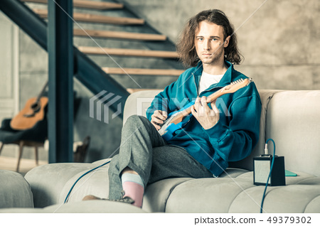 Handsome extraordinary man wearing stylish outfit while training his guitar skills 49379302