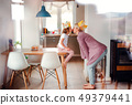 A portrait of small girl and mother with paper crown at home, kissing. 49379441