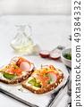 Toasts with avocado, radish and salmon. Healthy 49384332
