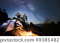 Man resting beside camp, bonfire and tourist tent at night 49385482