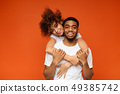 Cute african-american girl embracing her boyfriend from back 49385742