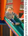 cute little toddler girl sliding down the children's slide 49387991