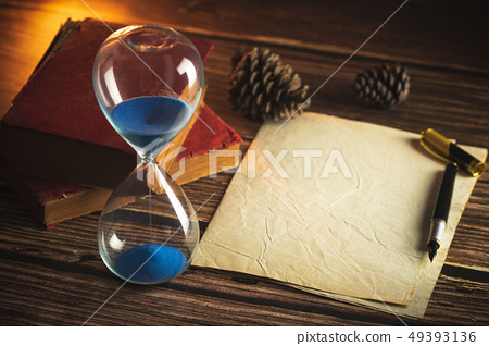 Hourglass and old books with old paper and pen. 49393136