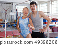 Female and male gymnasts standing near vaulting buck during workout 49398208