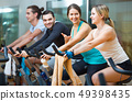 Group positive working out of cycling in fitness club 49398435