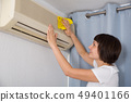 Woman cleaning air conditioner 49401166
