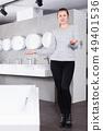 Positive girl customer buying ceramic bath in store 49401536