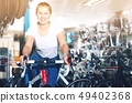 Portrait of girl who is standing with bicycle in store. 49402368