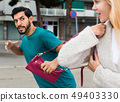Man is stole the handbag from stranger woman 49403330