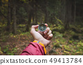 A beautiful male hand with a yellow watch strap holds a magnetic compass in the coniferous autumn 49413784